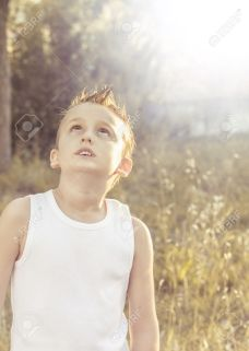20668139-child-looks-intrigued-into-the-sky-under-the-golden-sun-of-summer-stock-photo